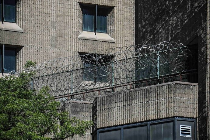 FILE - This Aug. 10, 2019, shows razor wire fencing at the Metropolitan Correctional Center in New York. Democratic lawmakers are raising questions about the federal Bureau of Prisons' release of high-profile inmates and are calling for widespread testing of federal inmates as the number of coronavirus cases has exploded in the federal prison system. (AP Photo/Bebeto Matthews, File)