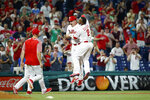 Philadelphia Phillies' Jay Bruce, left, and Jean Segura celebrate after Bruce drove in the winning run with a double off New York Mets relief pitcher Stephen Nogosek during the 10th inning of a baseball game, Wednesday, June 26, 2019, in Philadelphia. Philadelphia won 5-4. (AP Photo/Matt Slocum)