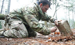 A student from the U.S. Army John F. Kennedy Special Warfare Center and School practices setting a paiute deadfall trap for small game during the survival phase of Survival Evasion Resistance and Escape Level-C training (SERE) at Camp Mackall, N.C., Feb. 28, 2019. Commanders are making big changes to the grueling course that soldiers must pass to join the elite Special Forces. The goal is to meet evolving national security threats and to shift from a culture that weeds out struggling soldiers to one that trains them to do better.(Ken Kassens/U.S. Army via AP)