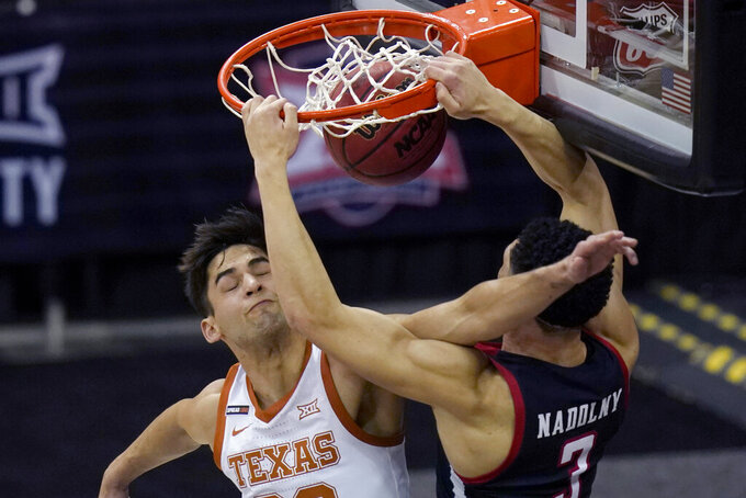 Texas Tech guard Clarence Nadolny (3) is fouled by Texas forward Brock Cunningham, left, during the first half of an NCAA college basketball game in the quarterfinal round of the Big 12 men's tournament in Kansas City, Mo., Thursday, March 11, 2021. (AP Photo/Orlin Wagner)