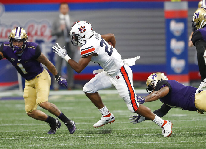 Auburn wide receiver Ryan Davis (23) breaks away from Washington defensive back Austin Joyner (4) as he returns a punt for a big gain in the first half of an NCAA college football game Saturday, Sept. 1, 2018, in Atlanta. (AP Photo/John Bazemore)