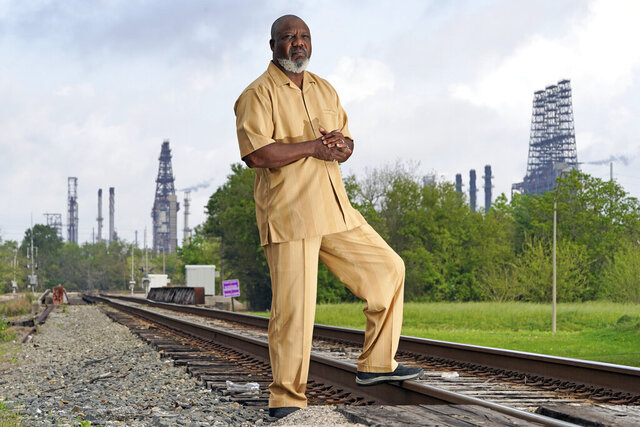 Activist Hilton Kelley poses along the railroad tracks that divide East and West Port Arthur Monday, March 23, 2020, in Port Arthur, Texas.