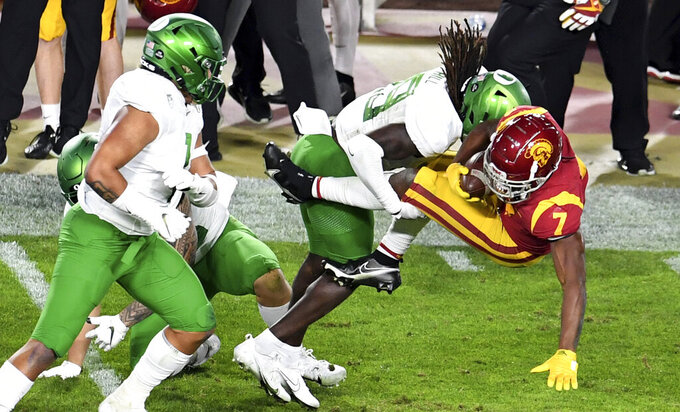 USC Running back Stephen Carr, right, runs for a first down and is tackled by Oregon safety Jamal Hill first half of an NCAA college football game at the Los Angeles Memorial Coliseum in Los Angeles on Friday, Dec. 18, 2020. (Keith Birmingham/The Orange County Register via AP)