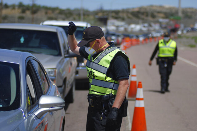 New Mexico state police officers screen cars for compliance with an emergency lockdown order that bans nonessential visitors and limits vehicle passengers to two people as they enter Gallup, N.M., Thursday, May 7, 2020. New Mexico Gov. Michelle Lujan Grisham renewed the lockdown order amid concerns about the rapid transmission of COVID-19 in the area. Gallup and surrounding McKinley County are one of the worst rural hot spots for coronavirus infections in the U.S. (AP Photo/Morgan Lee)