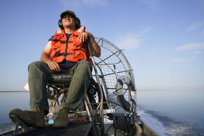 Jose Figueroa, with the California Fish and Wildlife Department, drives an air boat on the Salton Sea at the Sonny Bono Salton Sea National Wildlife Refuge in Calipatria, Calif., Thursday, July 15, 2021. California's largest but rapidly shrinking lake is at the forefront of efforts to make the U.S. a major global producer of lithium, the ultralight metal used in rechargeable batteries. Demand for electric vehicles has shifted investments into high gear to extract lithium from geothermal wastewater around the Salton Sea. (AP Photo/Marcio Jose Sanchez)