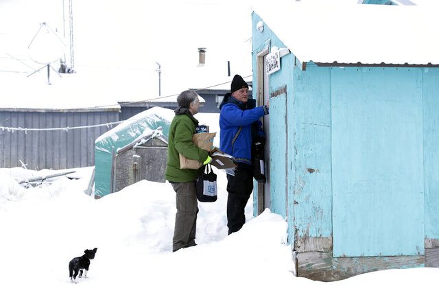FILE - In this Jan. 21, 2020, file photo, Census Bureau director Steven Dillingham, right, knocks on the door alongside census worker Tim Metzger as they arrive to conduct the first enumeration of the 2020 Census in Toksook Bay, Alaska. Thousands of census takers are about to begin the most labor-intensive part of America's once-a-decade headcount. The 2020 census started in January in rural Alaska where census takers visited homes much earlier than the rest of the country because of the difficulty in reaching those places. (AP Photo/Gregory Bull, File)