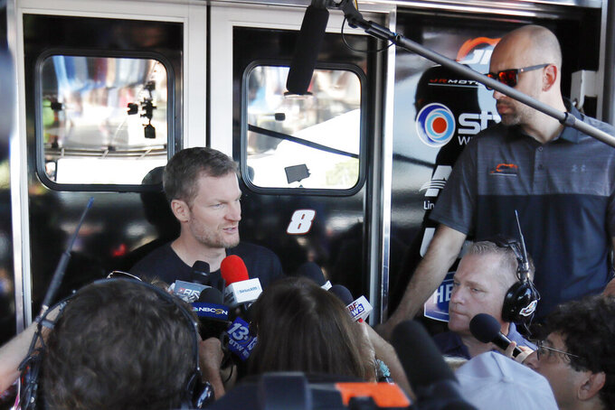Dale Earnhardt Jr talks with the media in the garage area before practice for a NASCAR auto race, Friday, Aug. 30, 2019, in Darlington, S.C. Earnhardt is scheduled to run in the Xfinity race on Saturday. (AP Photo/Terry Renna)