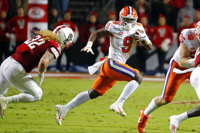 Clemson's Travis Etienne (9) runs away from North Carolina State's Drake Thomas (32) during the first half of an NCAA college football game in Raleigh, N.C., Saturday, Nov. 9, 2019. (AP Photo/Karl B DeBlaker)