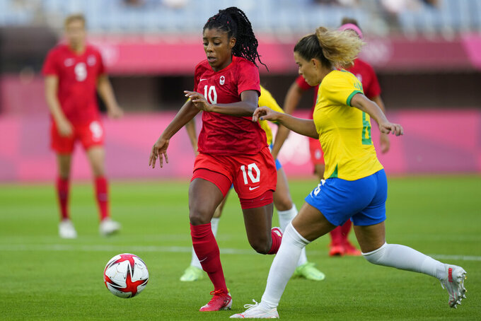 Brazil's Tamires, right, and Canada's Ashley Lawrence battle for the ball during a women's quarterfinal soccer match at the 2020 Summer Olympics, Friday, July 30, 2021, in Rifu, Japan. (AP Photo/Andre Penner)