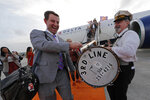 Clemson coach Dabo Swinney plays the cymbal on the drum of a member of the 3rd Line Brass Band as he arrives with the team for the NCAA College Football Playoff title game in New Orleans, Friday, Jan. 10, 2020. Clemson is scheduled to play LSU on Monday. (AP Photo/Gerald Herbert)