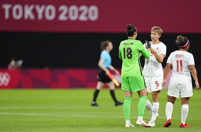 Canada's goalkeeper Kailen Sheridan, left, and Canada's Quinn, center, celebrate at the end of women's soccer match against Chile at the 2020 Summer Olympics, Saturday, July 24, 2021, in Sapporo, Japan. (AP Photo/Silvia Izquierdo)