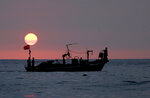 In this Thursday, Aug. 30, 2018 file photo, Lebanese fishermen sit at the bow of a fishing boat, in the Mediterranean Sea as the sun sets, at Ramlet al-Baida public beach, in Beirut, Lebanon. (AP Photo/Hussein Malla, File)