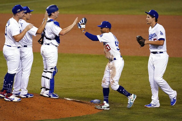 The Los Angeles Dodgers celebrate a 4-2 win over the Milwaukee Brewers in Game 1 of a National League wild-card baseball series Wednesday, Sept. 30, 2020, in Los Angeles. (AP Photo/Ashley Landis)