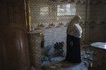 Khaldiya Nassir stands in her home, heavily damaged by airstrikes in the recent 11-day war in Beit Hanoun, northern Gaza Strip, Thursday, June 17, 2021. (AP Photo/Felipe Dana)