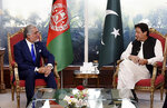 In this photo provided by Press Information Department, Abdullah Abdullah, left, chairman of Afghanistan's High Council for National Reconciliation, meets with Pakistan Prime Minister Imran Khan, in Islamabad, Pakistan, Tuesday, Sept. 29, 2020. Abdullah said that the time has come for the two neighboring countries to shun the suspicion,