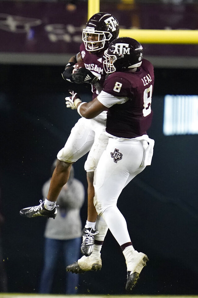 Texas A&M defensive back Jaylon Jones (17) reacts with teammate DeMarvin Leal (8) after intercepting a pass from LSU during the first half of an NCAA college football game, Saturday, Nov. 28, 2020, in College Station, Texas. (AP Photo/Sam Craft)