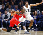 St. John's guard Greg Williams Jr., left, drives against Xavier guard KyKy Tandy (24) during the first half of an NCAA college basketball game, Sunday, Jan. 5, 2020, in Cincinnati. (AP Photo/Gary Landers)