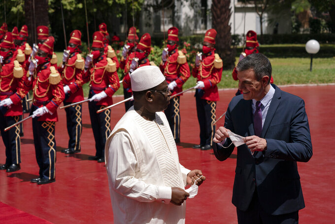 Senegal's President Macky Sall, left, welcomes Spanish Prime Minister Pedro Sanchez prior to a meeting at the presidential palace in Dakar, Senegal, Friday, April 9, 2021. Sanchez is on a mini-tour to Angola and Senegal that are key in the European country's new push to bolster ties with the neighboring continent and mitigate the migration flows that many fear could increase as a consequence of the coronavirus pandemic. (AP Photo/Leo Correa)