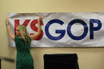 Shannon Golden prepares the stage for a GOP senatorial debate in Manhattan, Kan., Saturday, May 23, 2020. (AP Photo/Orlin Wagner)