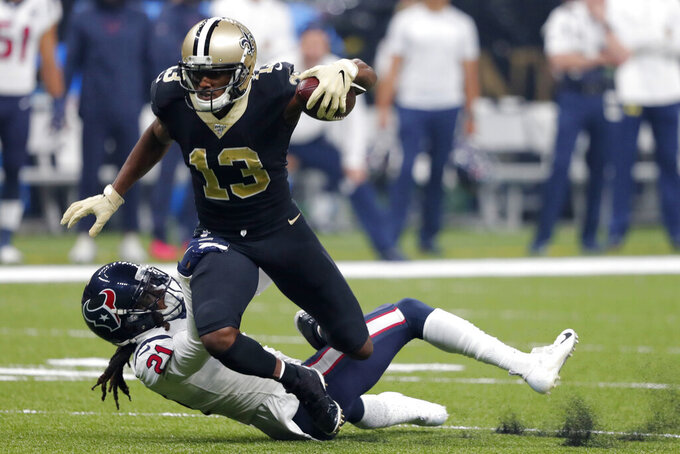 New Orleans Saints wide receiver Michael Thomas (13) tries to break a tackle by Houston Texans cornerback Bradley Roby (21) in the first half of an NFL football game in New Orleans, Monday, Sept. 9, 2019. (AP Photo/Bill Feig)