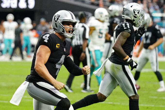 Las Vegas Raiders quarterback Derek Carr (4) celebrates after wide receiver Hunter Renfrow scored a touchdown against the Miami Dolphins during the second half of an NFL football game, Sunday, Sept. 26, 2021, in Las Vegas. (AP Photo/Rick Scuteri)