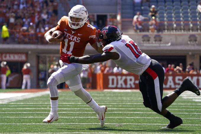 Texas quarterback Casey Thompson (11) tries to run past Texas Tech linebacker Jesiah Pierre (16) during the first half of an NCAA college football game on Saturday, Sept. 25, 2021, in Austin, Texas. (AP Photo/Chuck Burton)