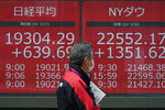 A man walks past an electronic stock board showing Japan's Nikkei 225 and New York Dow index at a securities firm in Tokyo Friday, March 27, 2020. Shares are mostly higher in Asia after stocks surged again on Wall Street with the approaching approval of a massive coronavirus relief bill by Congress. (AP Photo/Eugene Hoshiko)