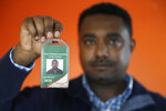 In this photo taken Sept. 24, 2019, Yonas Yeshanew, who resigned as Ethiopian Airline's chief engineer this summer and is seeking asylum in the U.S., poses with his company's identification card in the Seattle area. Yeshanew says in a whistleblower complaint filed with regulators that the carrier went into the maintenance records on a Boeing 737 Max jet a day after it crashed this year, a breach he contends was part of a pattern of corruption that included fabricating documents, signing off on shoddy repairs and even beating those who got out of line. (AP Photo/Elaine Thompson)