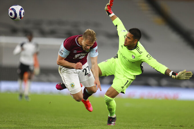 Burnley's Matej Vydra is challenged by Fulham's goalkeeper Alphonse Areola during the English Premier League soccer match between Fulham and Burnley at the Craven Cottage Stadium in London, Monday, May 10, 2021. (Catherine Ivill/Pool via AP)