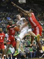 Oregon's Payton Pritchard, center, goes up for a shot between Houston's Dejon Jarreau, left, and Chris Harris Jr. during the second half of an NCAA college basketball game in Eugene, Ore., Friday, Nov. 22, 2019. (AP Photo/Chris Pietsch)