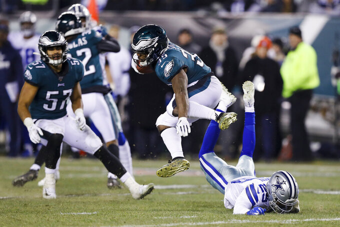 Philadelphia Eagles' Boston Scott (35) jumps over Dallas Cowboys' C.J. Goodwin during the second half of an NFL football game Sunday, Dec. 22, 2019, in Philadelphia. (AP Photo/Michael Perez)