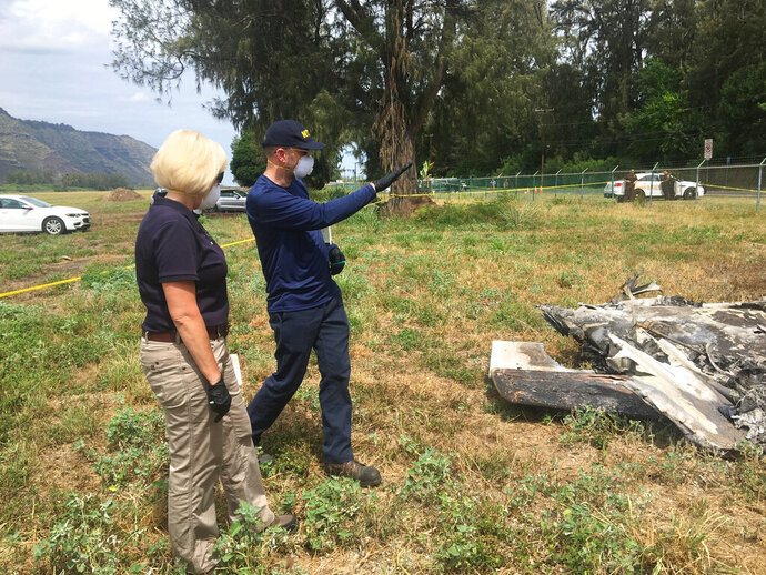 FILE - In this Sunday, June 23, 2019 file photo released by the National Transportation Safety Board, NTSB investigator Elliott Simpson, right, briefs NTSB Board Member Jennifer Homendy at the scene of a skydiving plane crash at Dillingham Airfield in Waialua, Hawaii. Federal officials released documents Wednesday, Oct. 28, 2020 that provide details about the 2019 crash that killed 11 people in Hawaii. The public docket contains reports from a National Transportation and Aviation Administration investigation into the crash. (National Transportation Safety Board via AP, File)