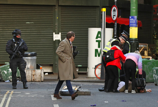 A person is assisted after falling when Police evacuated people from Borough Market on the south side of London Bridge in London, Friday, Nov. 29, 2019. British police say several people have stabbed near to London Bridge, and a man has been detained. The news came after witnesses reported hearing gunshots in the area. (AP Photo/Frank Augstein)