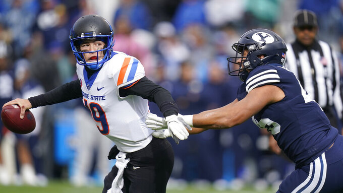 Boise State quarterback Hank Bachmeier (19) breaks free from BYU defensive lineman Pepe Tanuvasa (45) during the second half of an NCAA college football game Saturday, Oct. 9, 2021, in Provo, Utah. (AP Photo/Rick Bowmer)