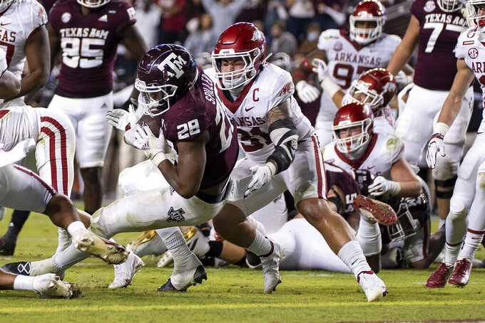 Texas A&M running back Isaiah Spiller (28) rushes for a touchdown against Arkansas linebacker Grant Morgan (31) during the second quarter of an NCAA college football game Saturday, Oct. 31, 2020, in College Station, Texas. (AP Photo/Sam Craft)