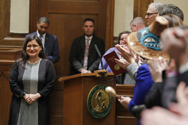 New Washington Supreme Court Justice Raquel Montoya-Lewis, left, reacts to applause after she was sworn in, Monday, Jan. 6, 2020, in Olympia, Wash. Montoya-Lewis was appointed by Gov. Jay Inslee to fulfill the remaining term of former Chief Justice Mary Fairhurst, who retired in January as she battles cancer. (AP Photo/Ted S. Warren)