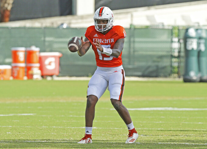 Miami Hurricanes quarterback Jarren Williams takes a snap during the NCAA college football team's practice Tuesday, Aug. 13, 2019, in Coral Gables, Fla. (David Santiago/Miami Herald via AP)