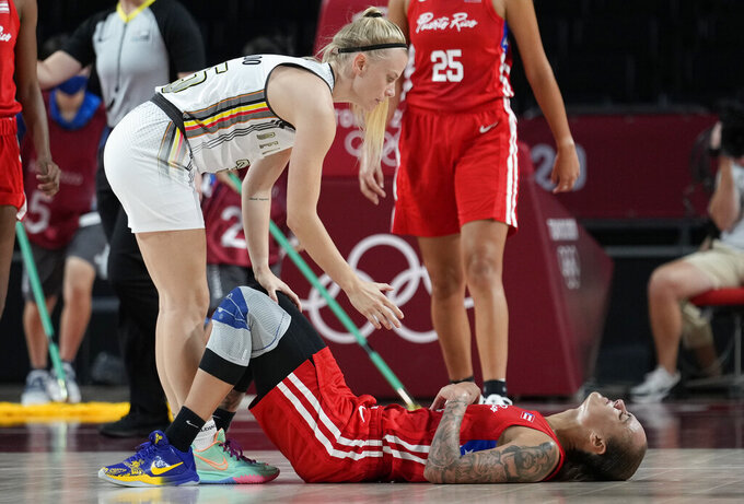 Belgium's Julie Vanloo (35), left, offers help to Puerto Rico's Jazmon Gwathmey (24) during women's basketball preliminary round game between Belgium and Puerto Rico at the 2020 Summer Olympics, Friday, July 30, 2021, in Saitama, Japan. (AP Photo/Eric Gay)