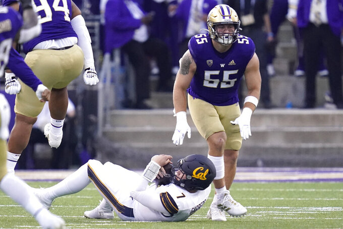 California quarterback Chase Garbers (7) gets up after being sacked by Washington linebacker Ryan Bowman (55) during the first half of an NCAA college football game, Saturday, Sept. 25, 2021, in Seattle. (AP Photo/Elaine Thompson)