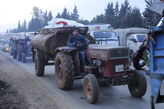 A man pulls a tanker trailer as civilians flee a Syrian military offensive in Idlib province on the main road near Hazano, Syria, Tuesday, Dec. 24, 2019. Syrian forces launched a wide ground offensive last week into the northwestern province of Idlib, which is dominated by al-Qaida-linked militants. The United Nations estimates that some 60,000 people have fled from the area, heading south, after the bombings intensified earlier this month. (AP Photo/Ghaith al-Sayed)