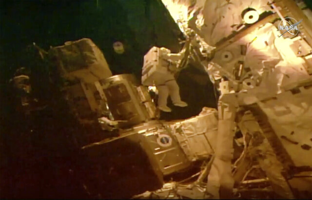 This photo provided by NASA shows astronauts Bob Behnken and Chris Cassidy on a spacewalk outside of the International Space Station on Tuesday, July 21, 2020. The astronauts are on their fourth and final spacewalk in under a month and instead of swapping batteries, they'll be routing cables and hooking up a tool storage chest.  (NASA via AP)