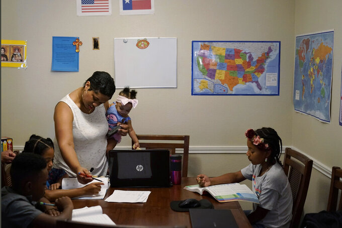 """Arlena Brown, center, holds her youngest child, Lucy, 9 months, as she leads their other children, from left, Jacoby, 11; Felicity, 9, and Riley, 10, through math practice at their home in Austin, Texas, Tuesday, July 13, 2021. Arlena worked as a preschool teacher before the pandemic. """"In the beginning, the biggest challenge was to unschool ourselves and understand that homeschooling has so much freedom,"""" she said. """"We can go as quickly or slowly as we need to."""" (AP Photo/Eric Gay)"""