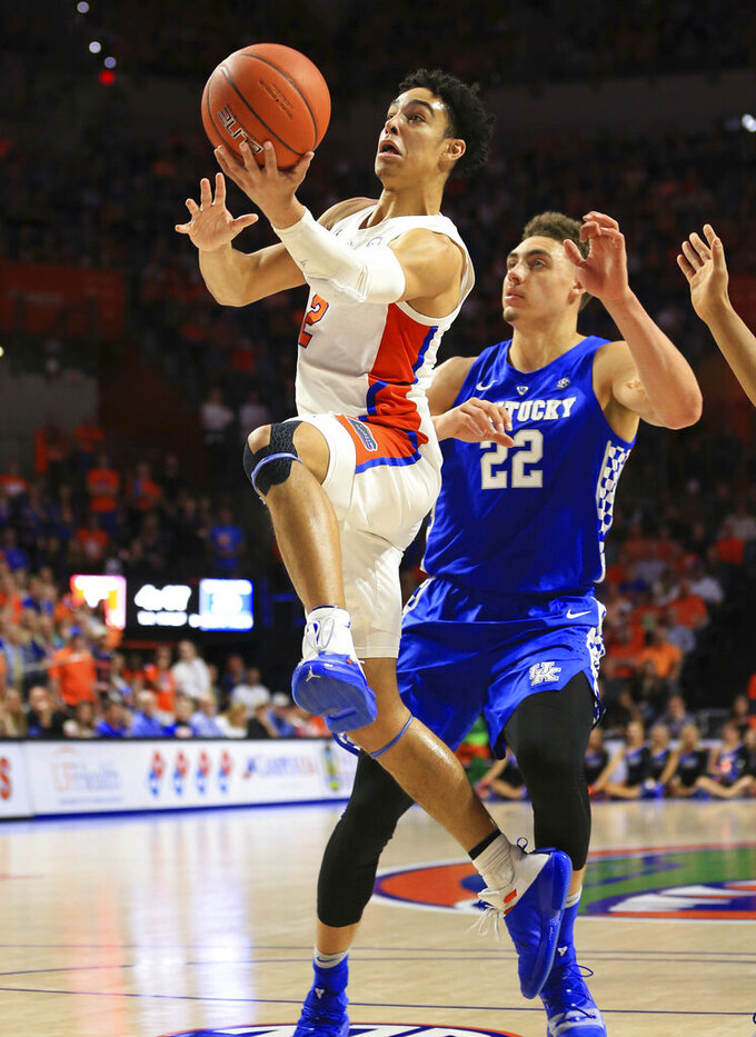 Florida guard Andrew Nembhard makes a layup past Kentucky forward Reid Travis during the first half of an NCAA college basketball game Saturday, Feb. 2, 2019, in Gainesville, Fla. (AP Photo/Matt Stamey)