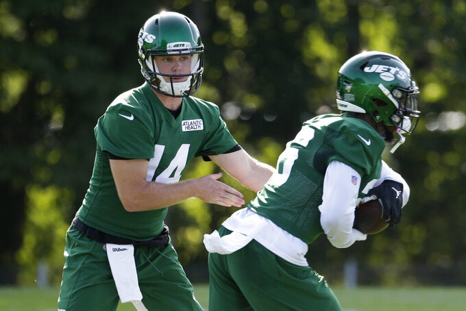 New York Jets quarterback Sam Darnold, left, hands off to Le'Veon Bell during practice at the NFL football team's training camp in Florham Park, N.J., Thursday, July 25, 2019. (AP Photo/Seth Wenig)