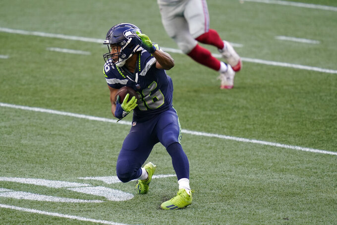 Seattle Seahawks wide receiver Tyler Lockett carries the ball before going down with an injury during the first half of an NFL football game against the New York Giants, Sunday, Dec. 6, 2020, in Seattle. (AP Photo/Elaine Thompson)