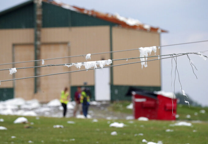 Insulations covers power lines at D and D Well and Pumps where a roof was torn off a storage shed on County Highway F in the Town of Concord, Wis., on Thursday, July 29, 2021. A line of thunderstorms arrived early Thursday generating numerous tornado warnings as well as high winds and near-constant lightning. (Mike De Sisti/Milwaukee Journal-Sentinel via AP)