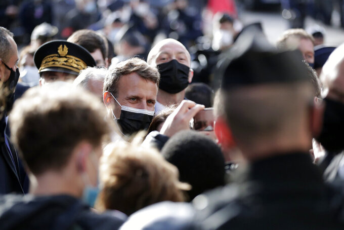 French President Emmanuel Macron speaks with local residents during a visit to mark the reopening of cultural activities after closures during the Covid-19 pandemic, in Nevers, central France, Friday, May 21, 2021. (AP Photo/Thibault Camus, Pool)