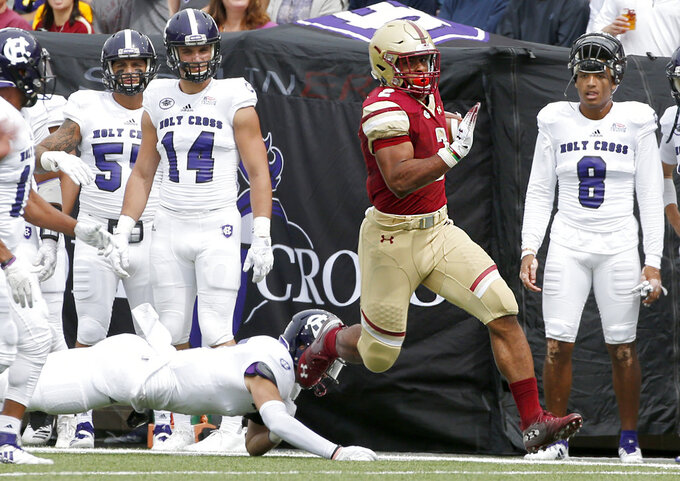 Boston College running back AJ Dillon (2) rushes down the sideline as Holy Cross players look on during the first half of an NCAA college football game, Saturday, Sept. 8, 2018, in Boston. (AP Photo/Mary Schwalm)