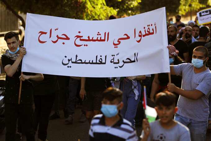 """Protesters carry an Arabic banner that reads: """"Save the Sheikh Jarrah neighborhood, Freedom for Palestine,"""" during a protest in support of Palestinians in the latest round of violence in Israel, in Beirut, Lebanon, Tuesday, May 11, 2021. A confrontation between Israel and Hamas sparked by weeks of tensions in contested Jerusalem escalated Tuesday. Israel unleashed new airstrikes on Gaza, killing a number of militants and civilians, while militants barraged southern Israel with hundreds of rockets, killing two Israelis. (AP Photo/Hussein Malla)"""