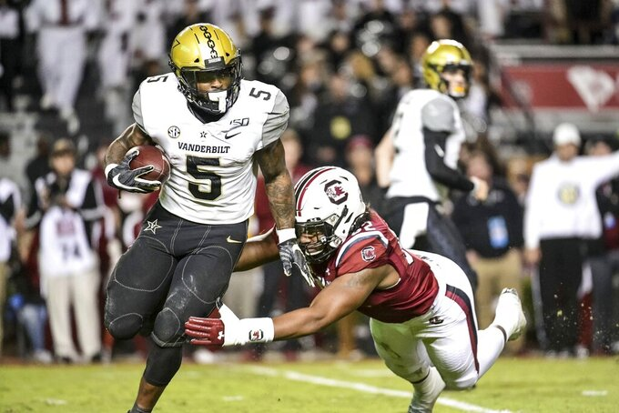 Vanderbilt running back Ke'Shawn Vaughn (5) runs with the ball as South Carolina defensive lineman Kingsley Enagbare (52) tries to make the tackle during the second half of an NCAA college football game Saturday, Nov. 2, 2019, in Columbia, S.C. South Carolina defeated Vanderbilt 24-7. (AP Photo/Sean Rayford)